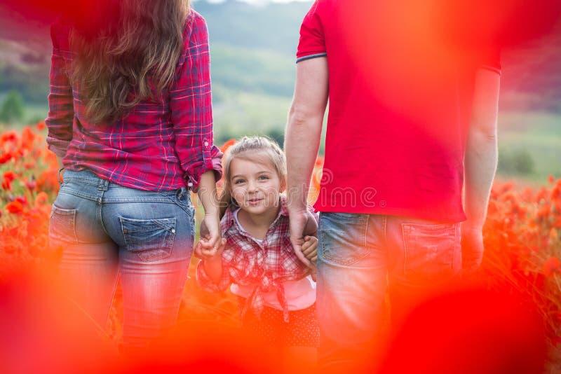 Familie auf dem Mohnblumenfeld stockfoto