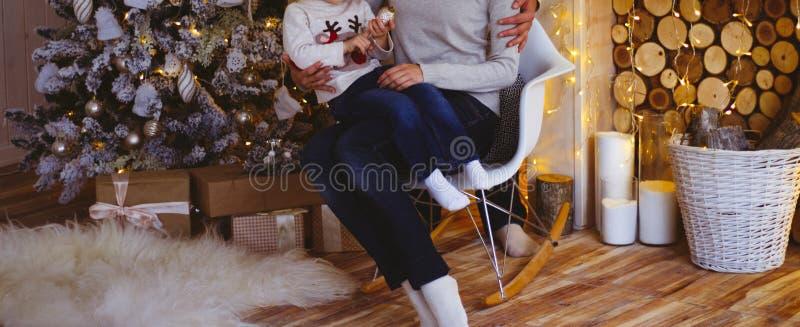 Familie auf dem Stuhl nahe dem Weihnachtsbaum Verziertes Wohnzimmer mit traditionellem Feuerplatz Gemütlicher warmer Winter zu Ha stockfotos