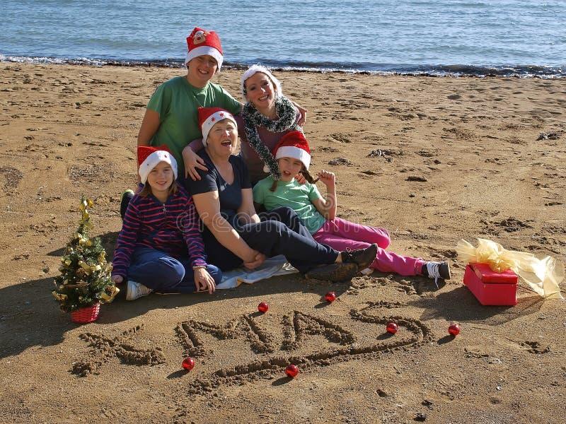 Familie auf den Strand-Gesang Weihnachtslieden stockfotografie