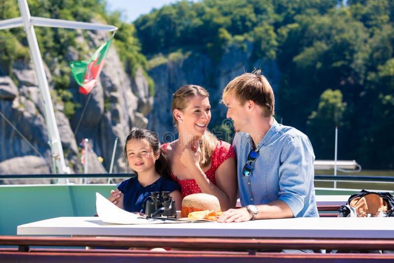 Familie auf der Flusskreuzfahrt, die Berge von der Schiffsplattform betrachtet stockfotos