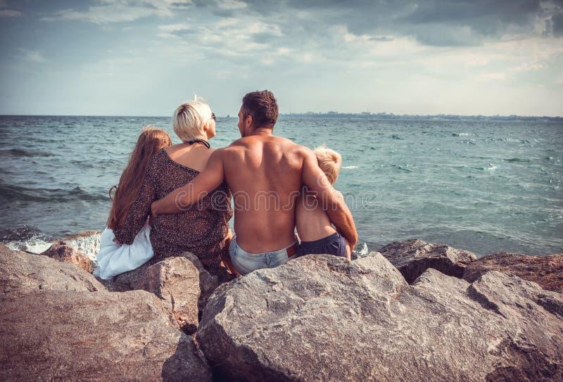 Familie auf der Steinküste nahe dem Meer lizenzfreie stockfotos