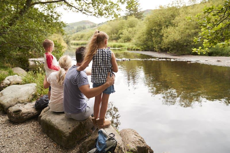 Familie auf der Wanderung, die heraus über Fluss im BRITISCHEN See-Bezirk schaut stockbilder