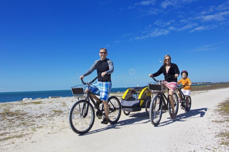 Familie auf einer Strandfahrradfahrt zusammen stockbild