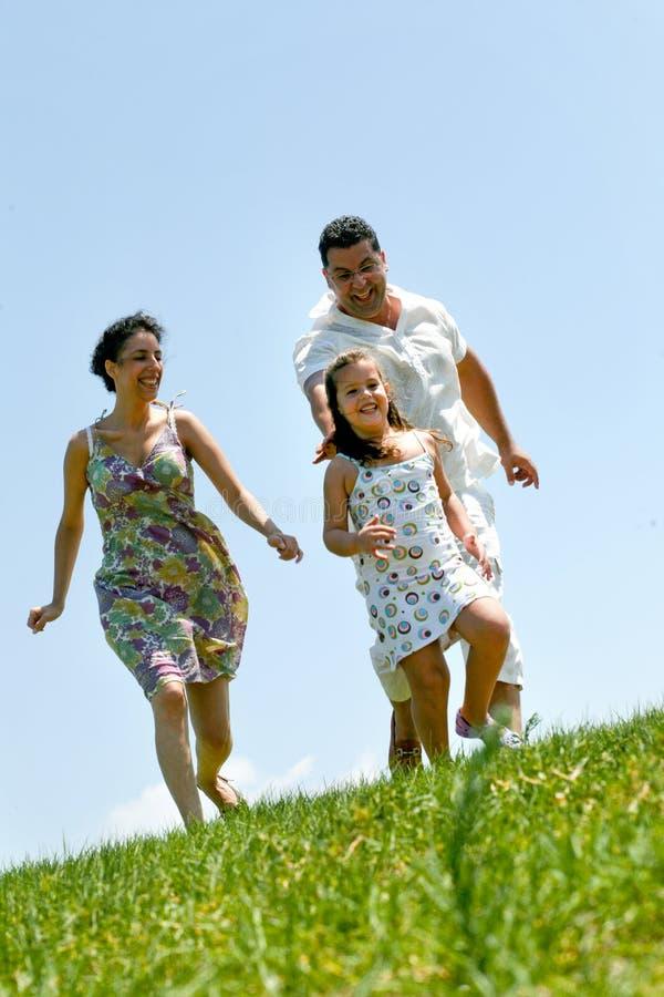 Familie auf Kraut unter blauem Himmel stockbild