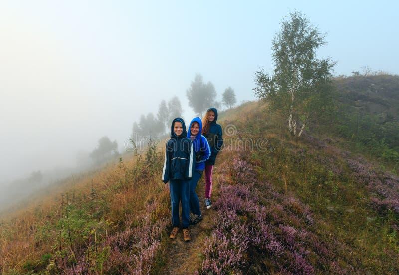Familie auf nebelhafter Morgentaubergwiese stockbilder