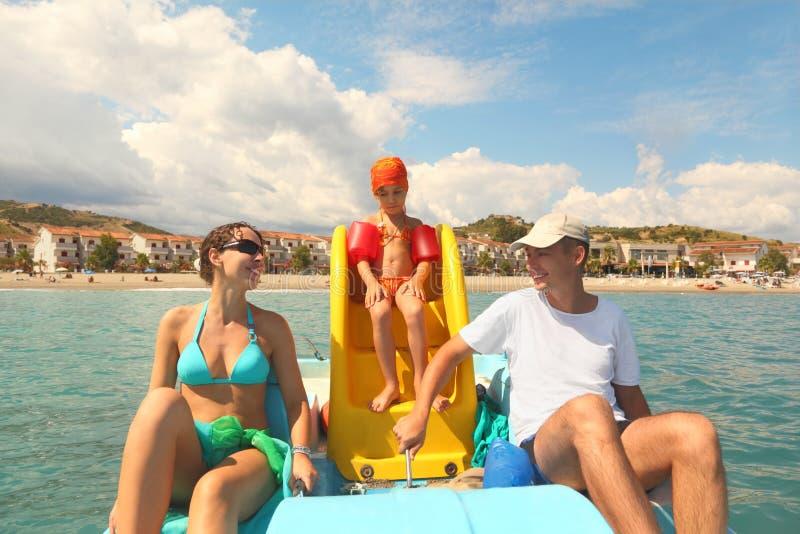 Familie auf Pedalboot mit Plättchen im Meer lizenzfreies stockbild