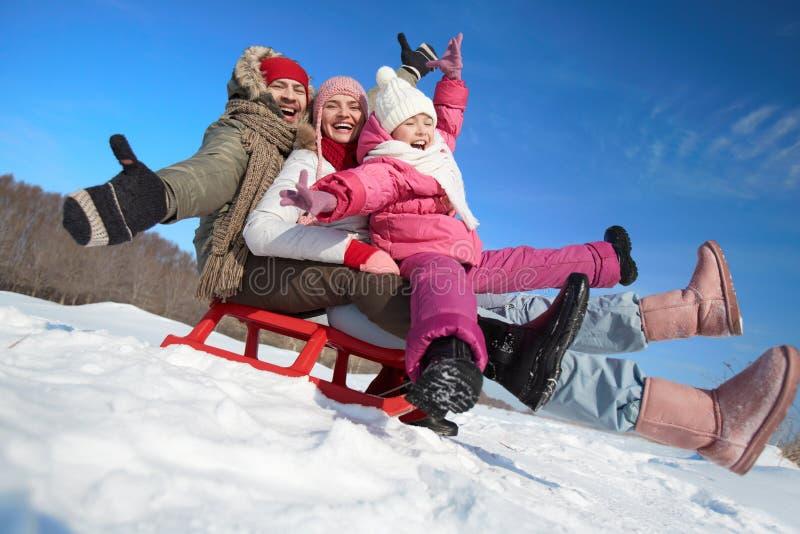Familie auf Schlitten lizenzfreies stockfoto