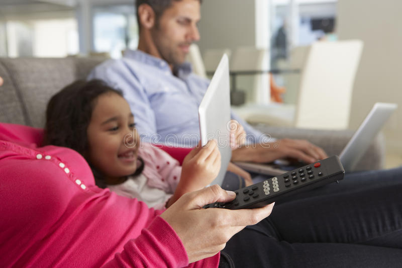 Familie auf Sofa With Laptop And Digital-Tablet fernsehend lizenzfreies stockfoto