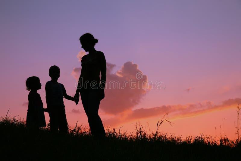 Familie auf Sonnenuntergang lizenzfreie stockfotos