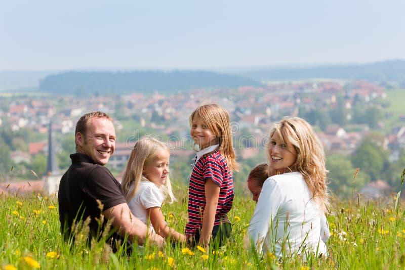Familie auf Wiese im Frühjahr oder Frühsommer lizenzfreie stockfotos