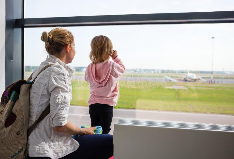 Familie bij de luchthaven die vliegtuigen bekijken stock fotografie