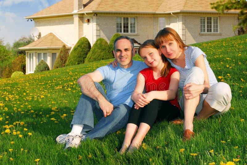 Familie bij een huis stock afbeelding
