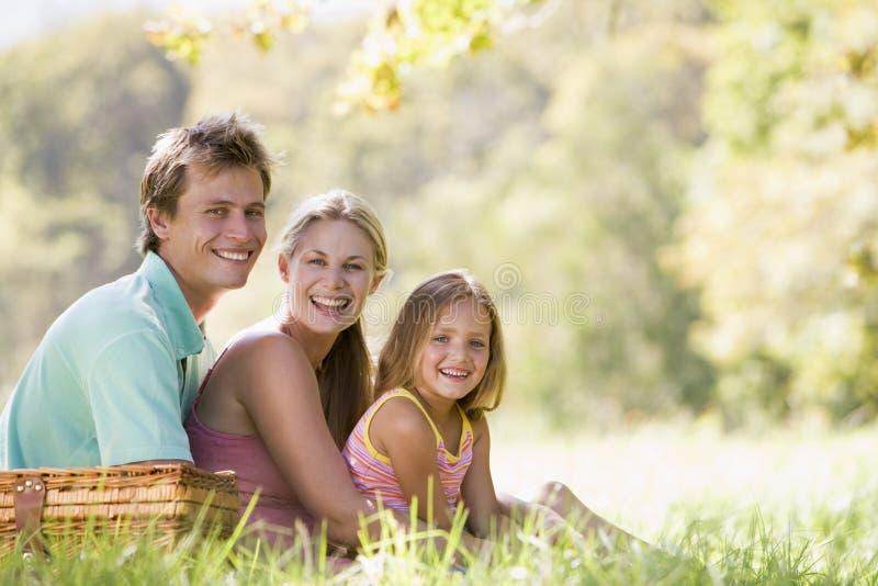 Familie bij park dat een picknick en het glimlachen heeft stock afbeeldingen