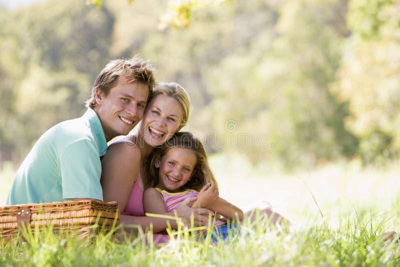 Familie bij park dat een picknick en het lachen heeft royalty-vrije stock foto's