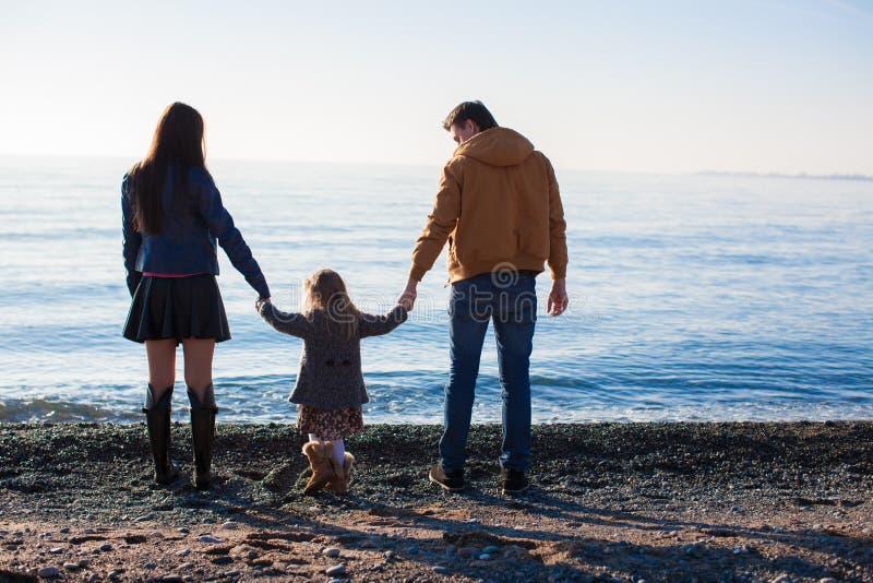 Familie bij wild strand tijdens de warme winter stock foto