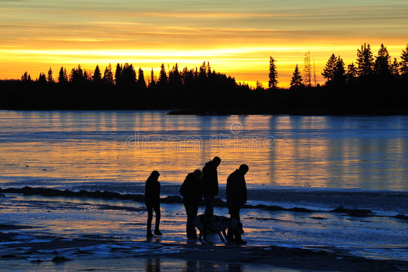 Familie bij zonsondergang stock foto's