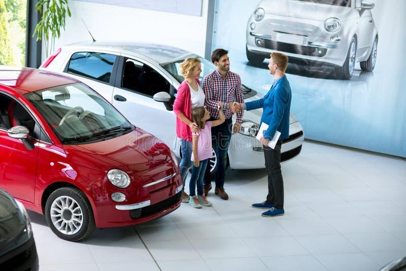 Familie binnen bij de zaal van het autohandel drijven royalty-vrije stock foto's