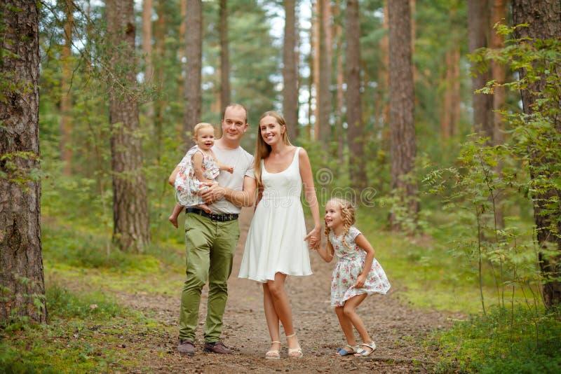 Familie - blondes durch gehen der Mutter, des Vaters und zwei Töchter lizenzfreies stockbild