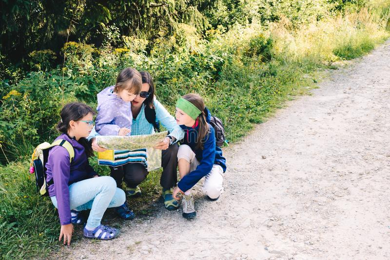 Familie in de bergen tijdens het beklimmen Mamma met dochters op een reis in de bergen Binnen bestuderend de kaart - een bergweg royalty-vrije stock afbeeldingen
