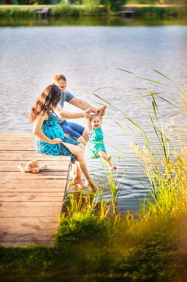 Familie in de zomer op een picknick dichtbij een vijver, water Familievakantie in aard Een kleine dochter met haar vader en een z stock foto