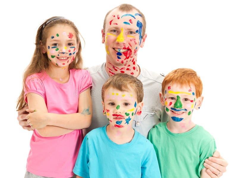 Familie der Kinder und des Vatis mit unordentlichen gemalten Gesichtern stockbild