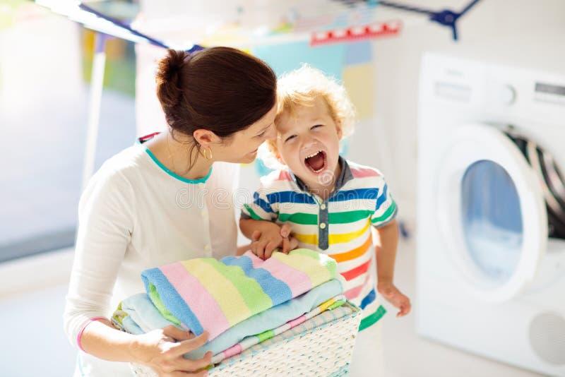 Familie in der Waschk?che mit Waschmaschine lizenzfreie stockfotografie