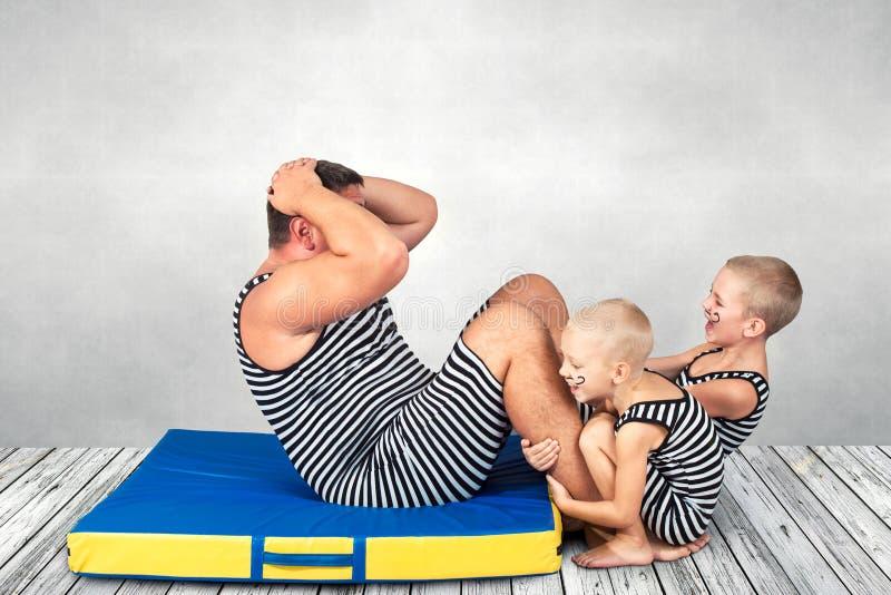 Familie des starken Mannes Der Vater von zwei Söhnen im Weinlesekostüm von Athleten schwingen Presse stockfotografie