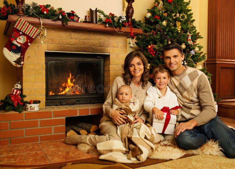 Familie dichtbij open haard in Kerstmishuis royalty-vrije stock afbeelding