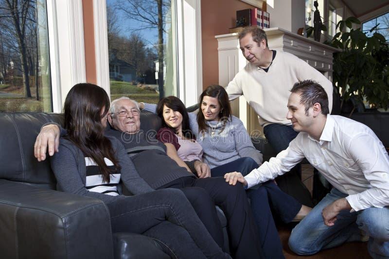 Familie, die älteren Verwandten an einem Ruhestand h besucht lizenzfreies stockbild