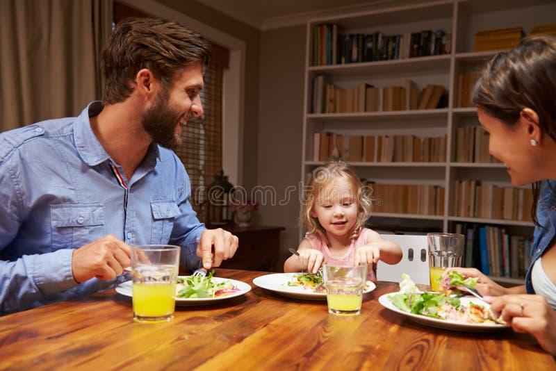 Familie, die Abendessen an einem Speisetische isst stockbilder