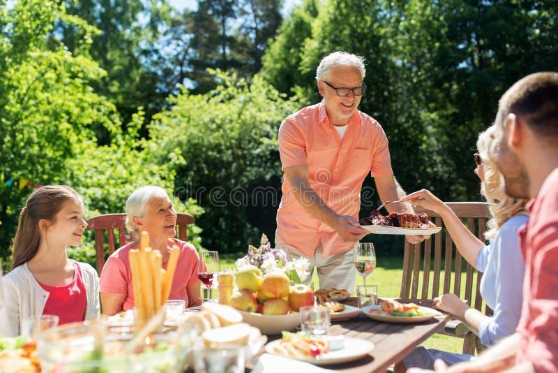 Familie, die Abendessen oder Grill am Sommergarten hat lizenzfreie stockfotografie