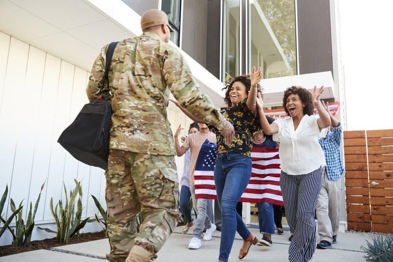 Familie die achter millennial Afrikaanse Amerikaanse militair welkom heten die huis, lage hoekmening terugkeren stock afbeeldingen