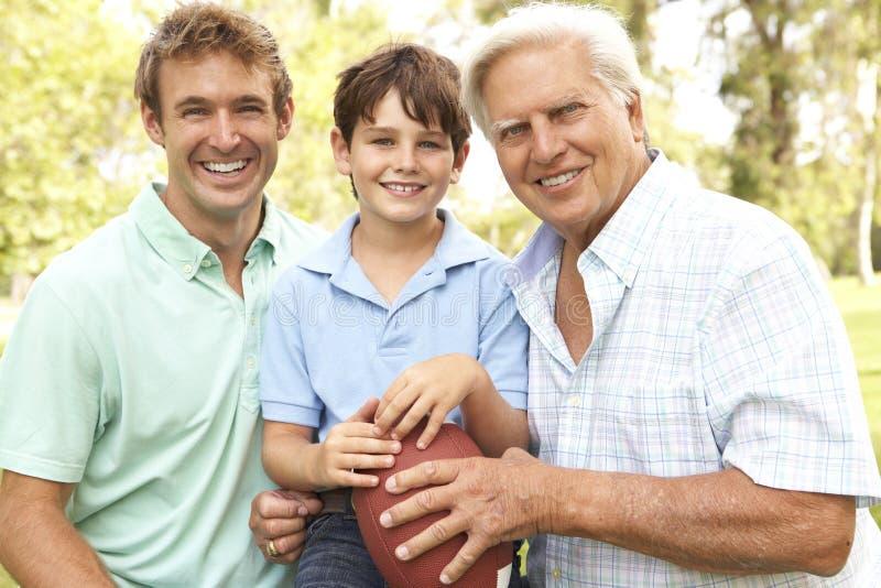Familie, die amerikanischen Fußball spielt stockfotografie