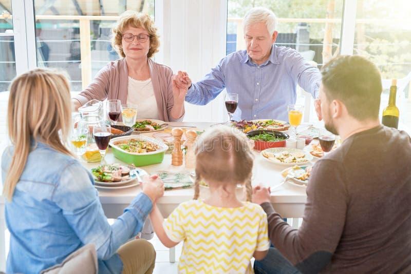 Familie, die Anmut am Abendessen sagt lizenzfreies stockfoto