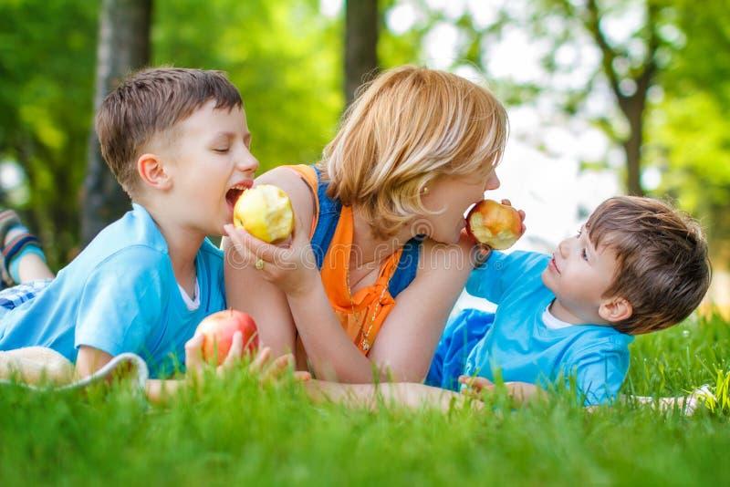 Familie die appel in de aard eten stock foto's