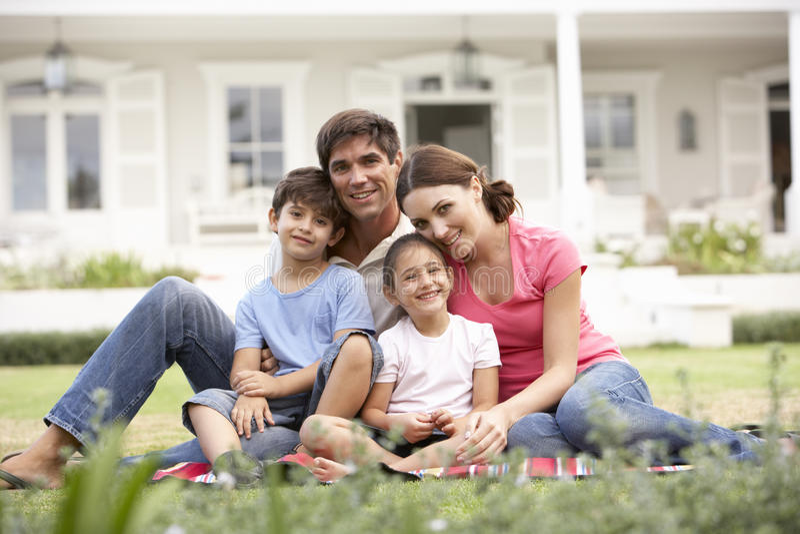 Familie, die außerhalb des Hauses auf Rasen sitzt stockbild