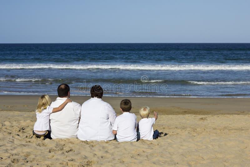 Familie, die auf überwachendem Ozean des Strandes sitzt stockfotos