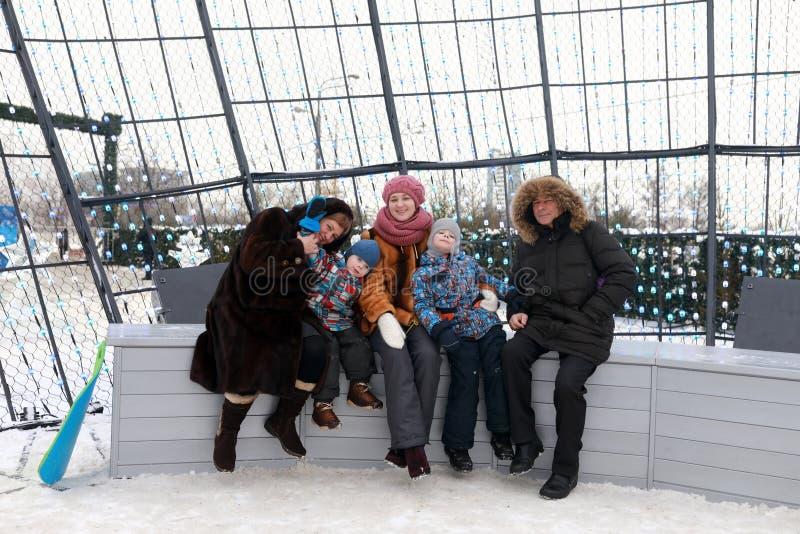 Familie, die auf Bank sitzt stockfotografie