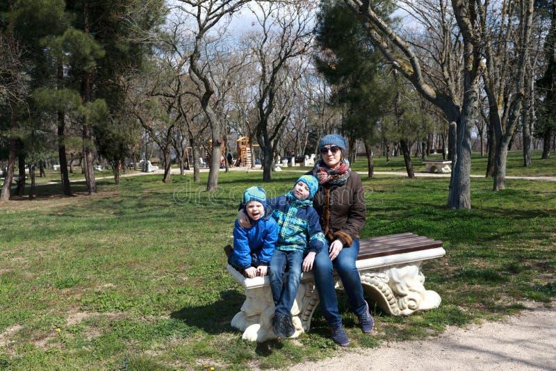Familie, die auf Bank sitzt stockfotos