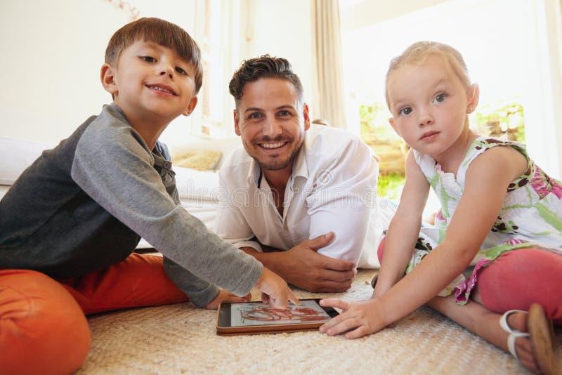 Familie, die auf Boden unter Verwendung der digitalen Tablette sitzt lizenzfreies stockbild
