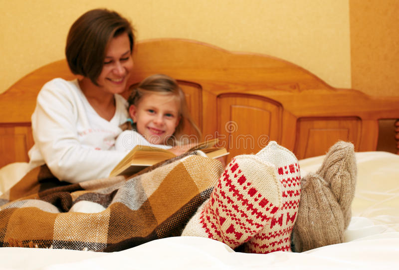 Familie, die auf dem Bett in gestrickten Socken liegt stockfoto