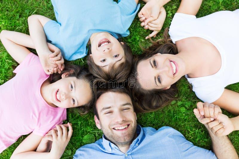 Familie, die auf dem Graslächeln liegt stockbilder