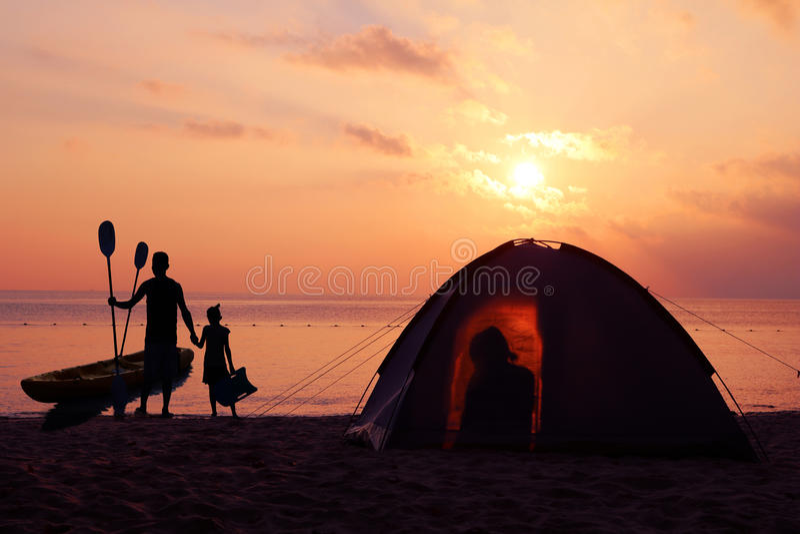 Familie, die auf dem Strand mit rotem Himmelsonnenuntergang kampiert und Kayak fährt stockfoto