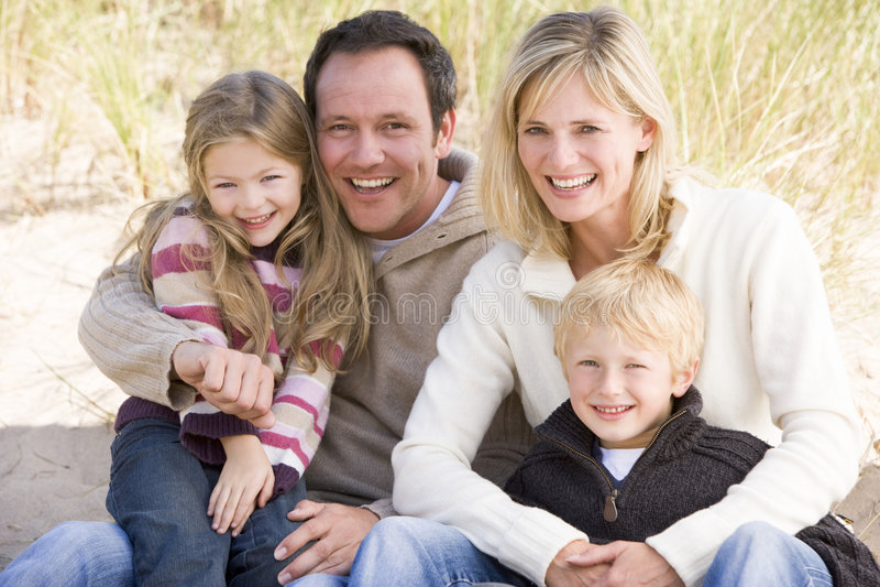 Familie, die auf dem Strandlächeln sitzt lizenzfreie stockbilder