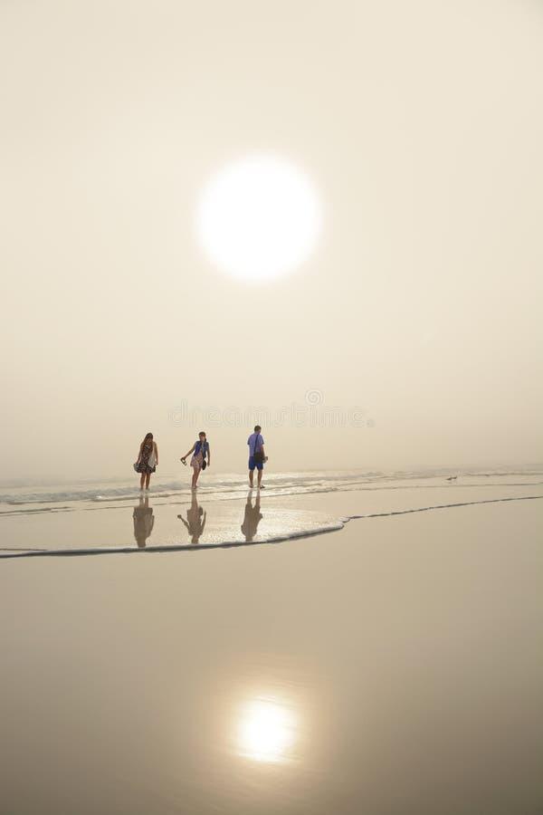 Familie, die auf den schönen Strand bei Sonnenaufgang geht lizenzfreie stockfotos