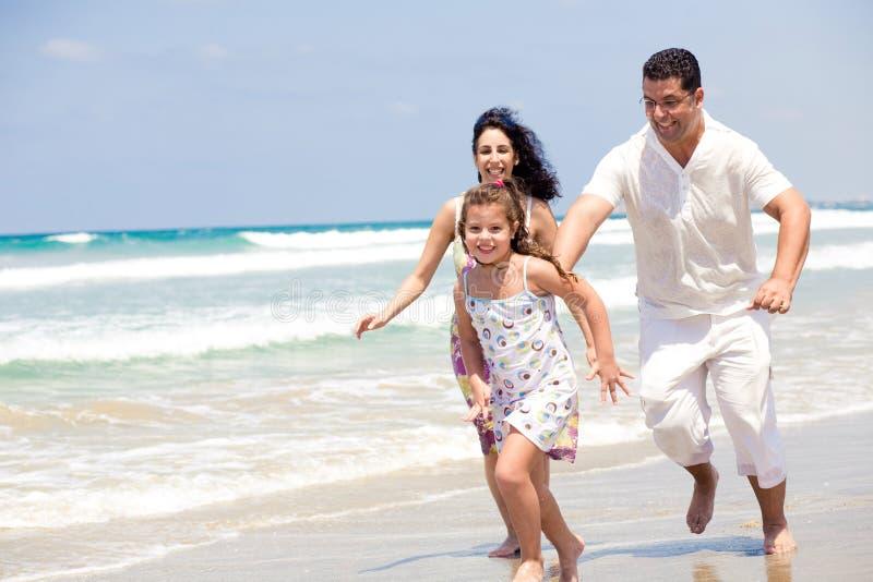 Familie, die auf den Strand läuft stockfotografie