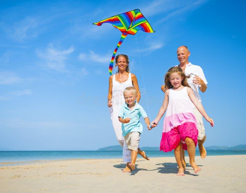 Familie, die auf den Strand läuft stockfotos