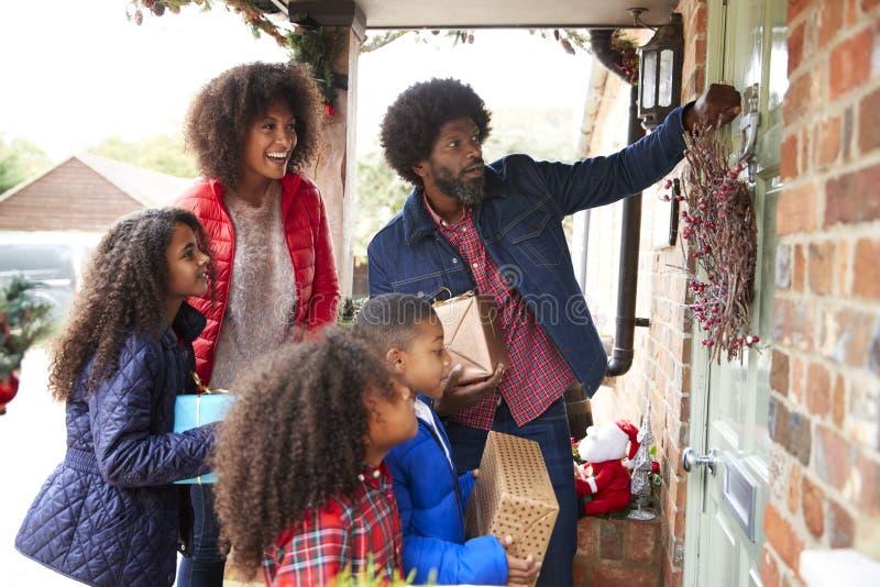 Familie, die auf Front Door As They Arrive für Besuch am Weihnachtstag mit Geschenken klopft lizenzfreies stockfoto
