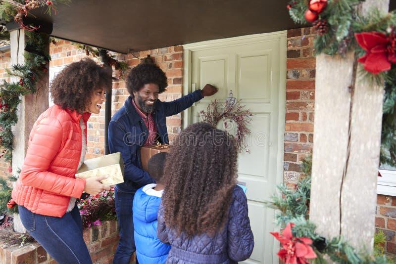 Familie, die auf Front Door As They Arrive für Besuch am Weihnachtstag mit Geschenken klopft lizenzfreies stockbild