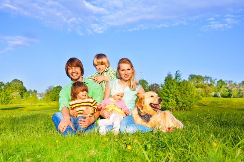 Familie, die auf grünem Gras mit Hund sitzt stockfoto